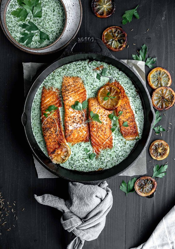 crispy salmon in a cast iron skillet with cream schug sauce, seared lemons and a bowl of schug to the side