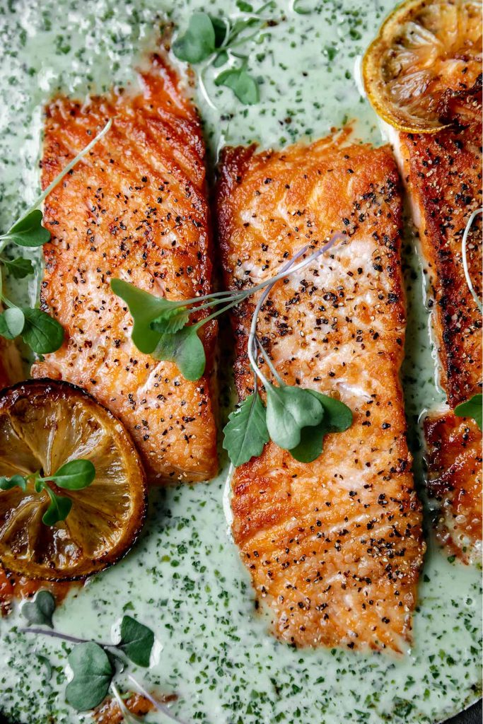 crispy seared salmon in a creamy green schug sauce with seared lemons