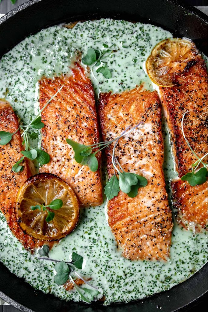 cast iron salmon with creamy schug and a roasted lemon