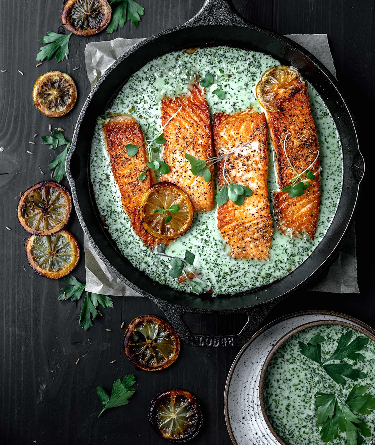 Salmon in a cast iron skillet with a creamy coconut schug sauce and roasted lemons