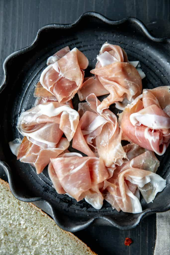 prosciutto twisted up on a black plate