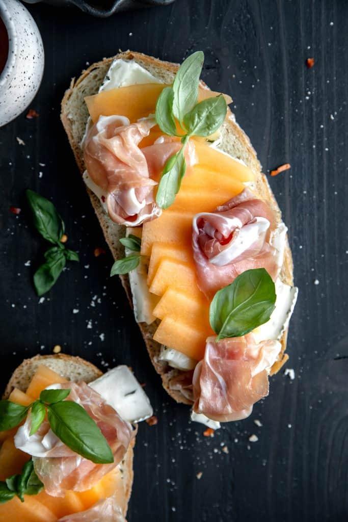 close up of the brie, prosciutto, basil and cantaloupe on panini bread
