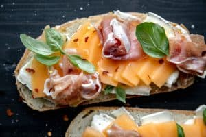 panini bread layered with brie, cantaloupe, hot honey, basil, prosciutto and crushed red pepper