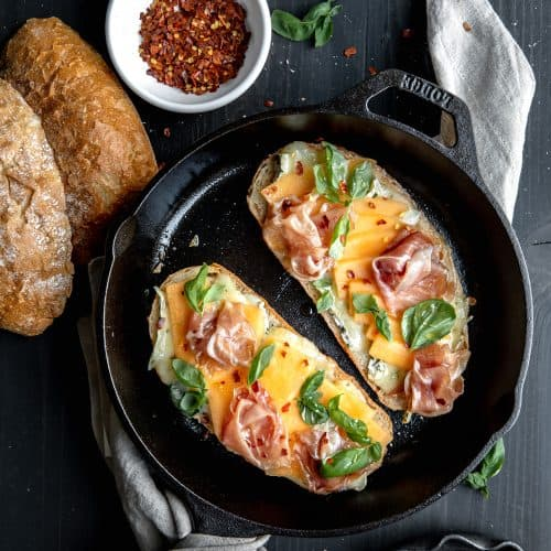 Prosciutto and melon panini topped with hot honey, chile flakes and brie cheese in a cast iron skillet