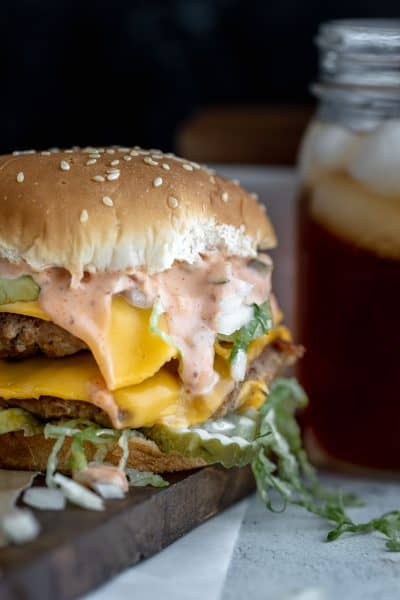 The ultimate pork burger with special sauce and a glass of iced tea