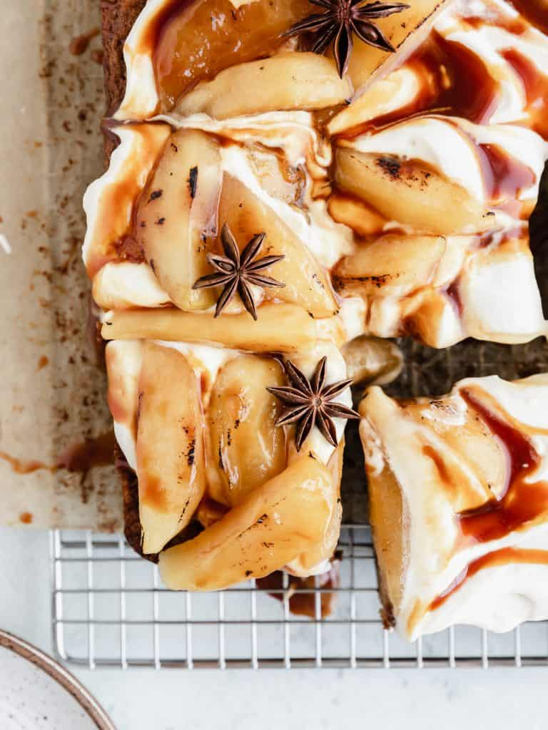 caramel apple snack cake topped with bruleed apples, frosting and caramel sauce