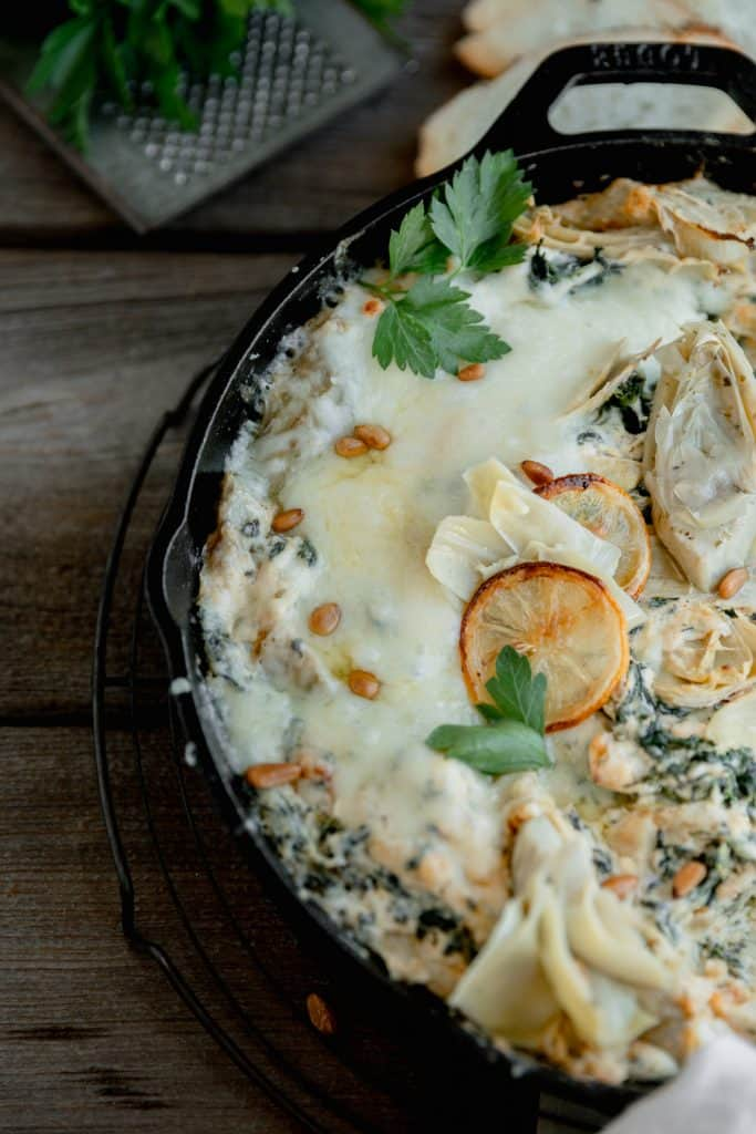 cast iron skillet with hot spinach and artichoke dip