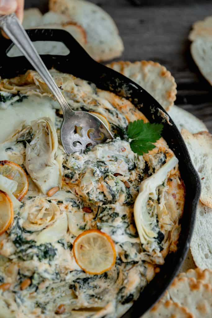 roasted garlic spinach artichoke dip with a spoon serving some out of the dish
