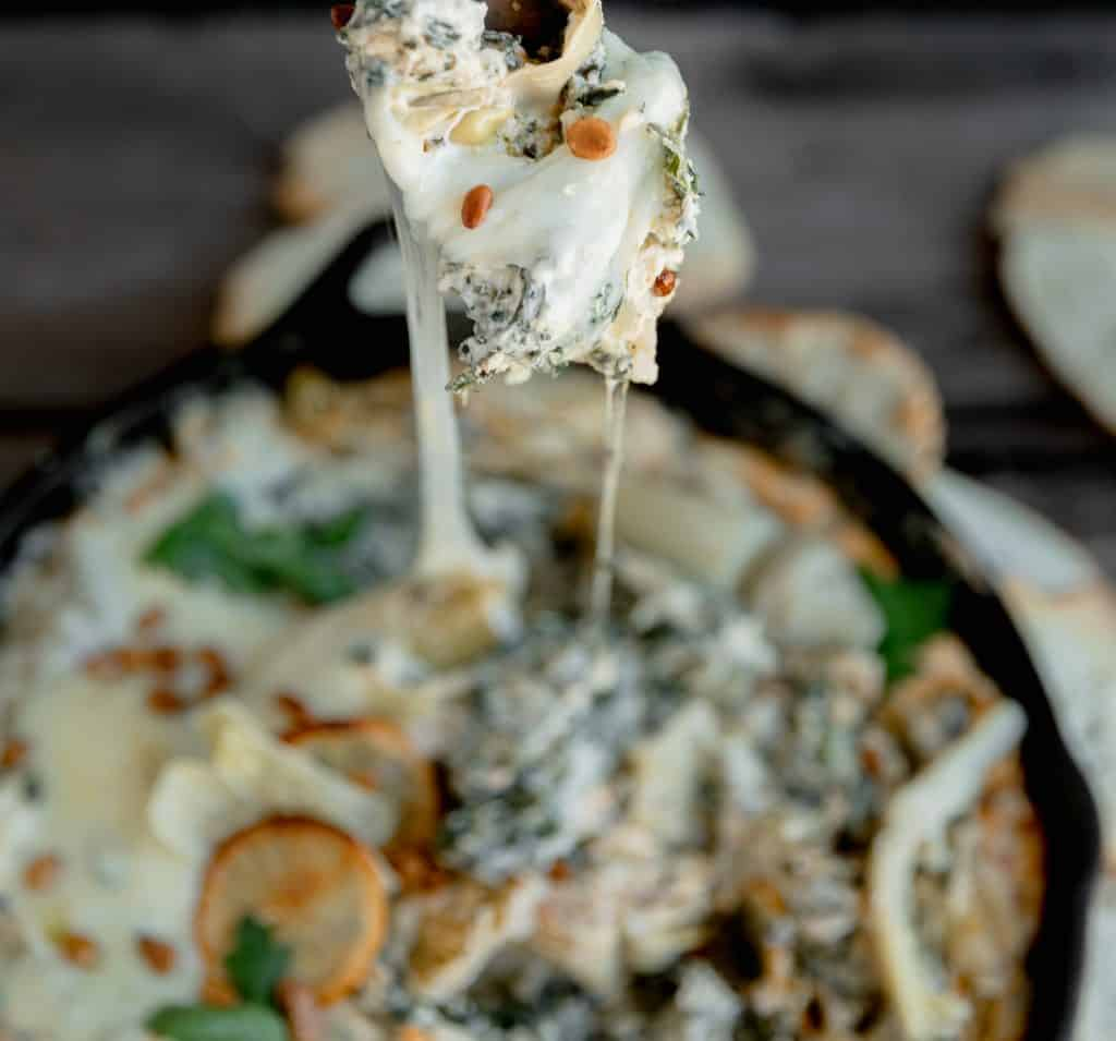 cheese pull on the spinach and artichoke dip