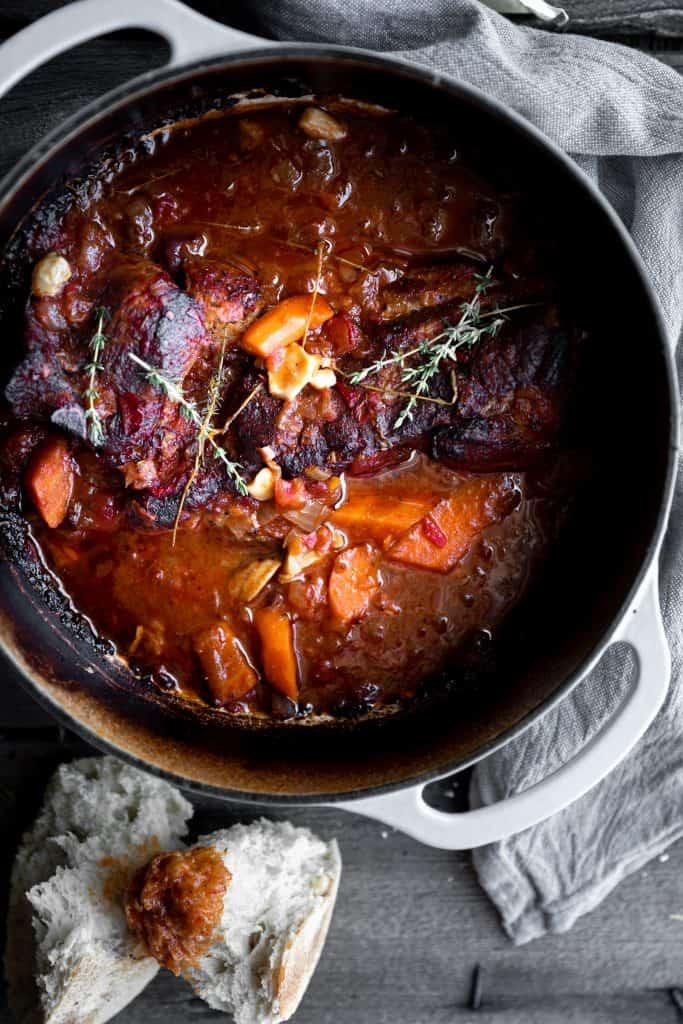 pork, tomato, wine, onion, carrots braising in a pot