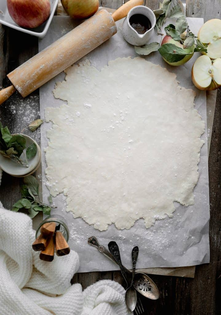homemade crust rolled out onto a flour surface with rolling pin surrounded by apples