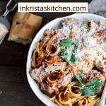 pork sugo in a bowl with parmesan cheese