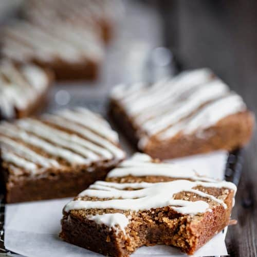 chewy molasses blondies with white chocolate drizzled over the top with a bite taken out of one of them
